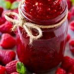 A jar of homemade raspberry sauce surrounded by fresh raspberries.