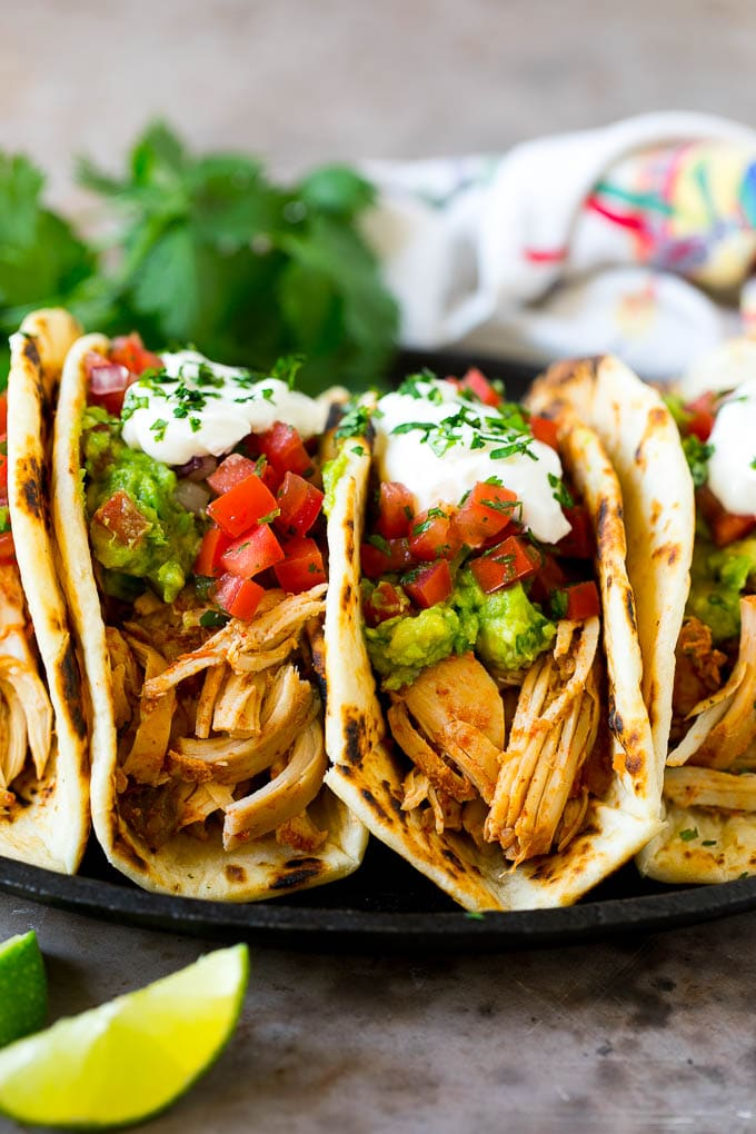 A plate of slow cooker chicken tacos topped with guacamole, pico de gallo and sour cream.