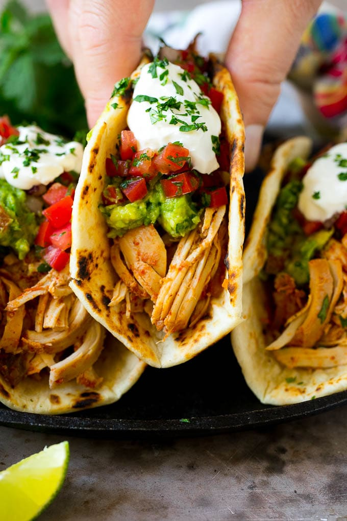 A hand picking up a slow cooker chicken taco.