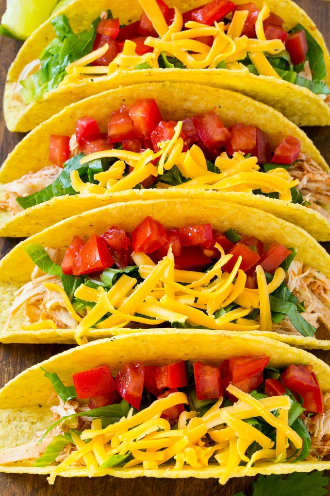 A row of crispy slow cooker chicken tacos filled with chicken, cheese, lettuce and tomatoes.