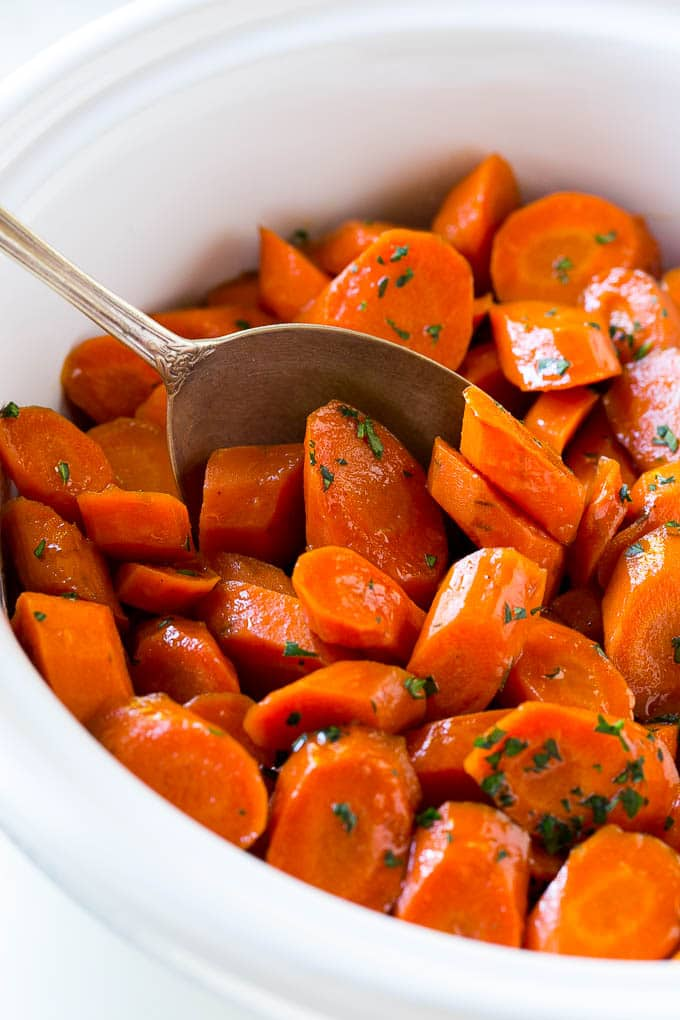 A crock pot of slow cooker carrots with a serving spoon in it.