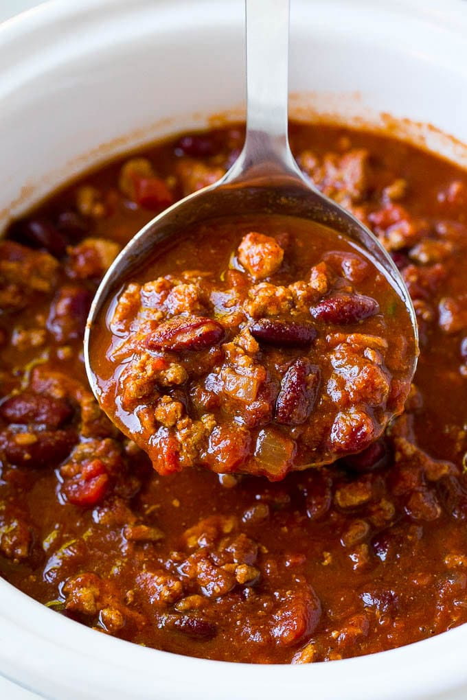 A ladle serving up a portion of slow cooker turkey chili.