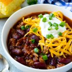 A bowl of slow cooker turkey chili topped with cheese.
