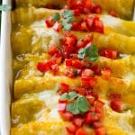 A pan full of green chile chicken enchiladas topped with diced tomatoes and cilantro.