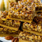 A serving platter full of pecan pie bars.