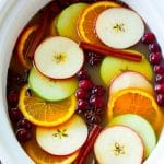 Slow cooker apple cider garnished with apple slices, oranges, cranberries, cinnamon sticks and spices.