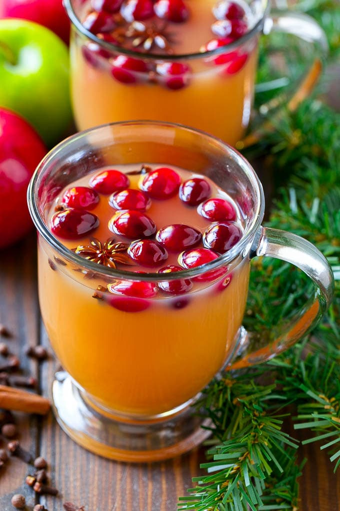 Mugs of slow cooker apple cider garnished with cranberries.