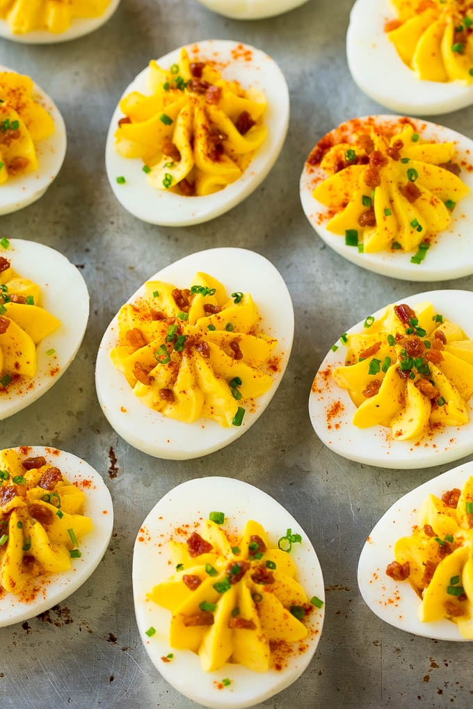 Bacon deviled eggs topped with chives and paprika on a sheet pan.