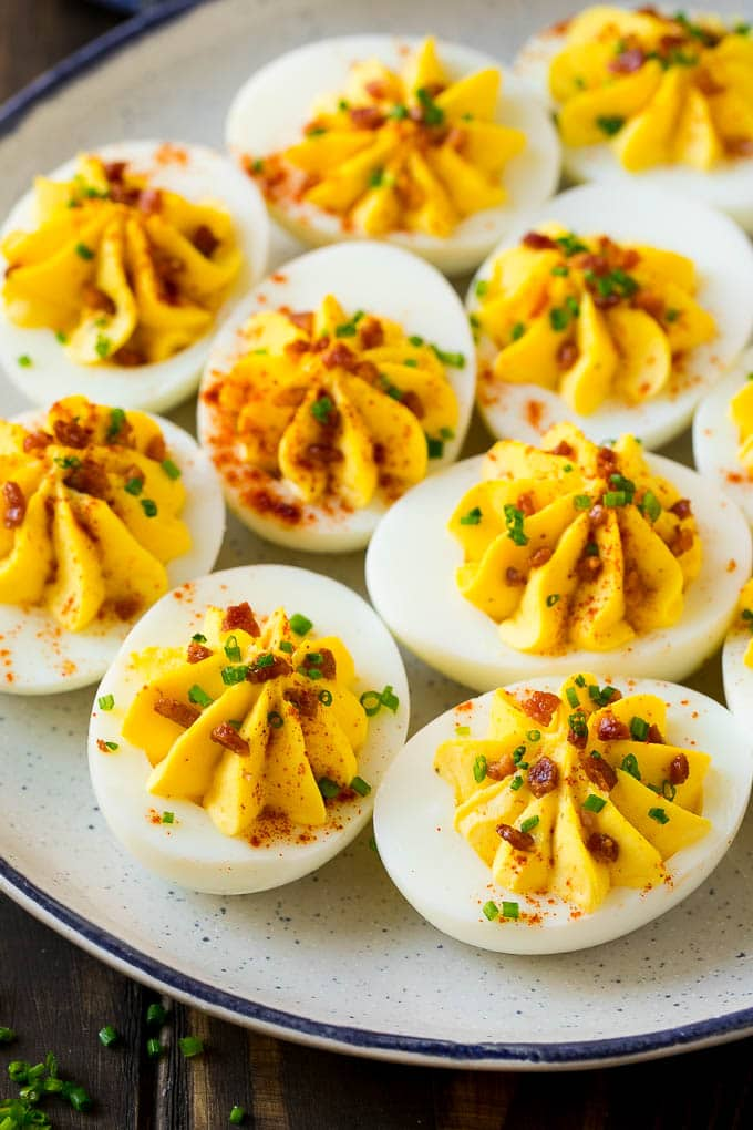 A plate of bacon deviled eggs garnished with sliced chives and smoked paprika.