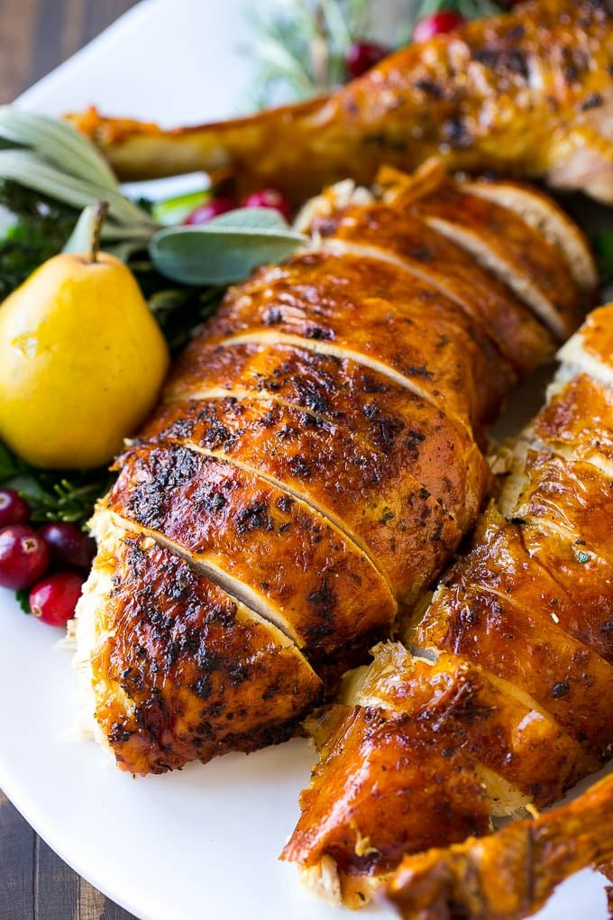 Herb roasted turkey sliced on a platter is the perfect holiday main course.