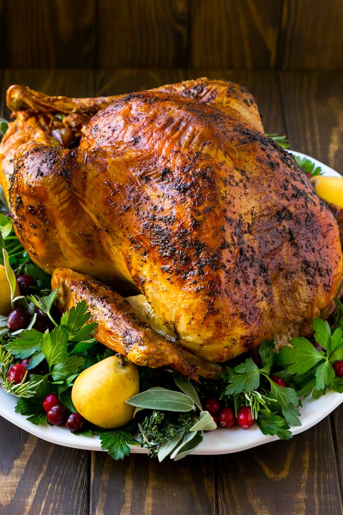 A whole herb roasted turkey surrounded by herbs and fruit.