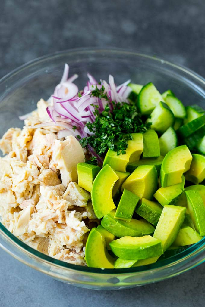 Tuna, onions, cucumber, avocado and cilantro in a mixing bowl.
