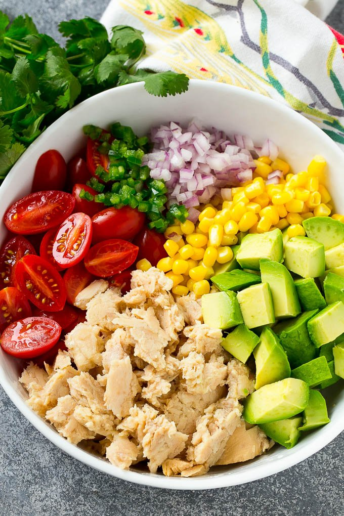 Ingredients for avocado tuna salad arranged in a bowl.