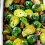 A dish of bacon roasted brussels sprouts with parsley.
