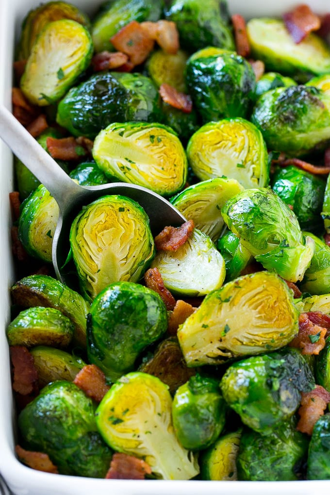 A serving dish full of roasted brussels sprouts with bacon and parsley.