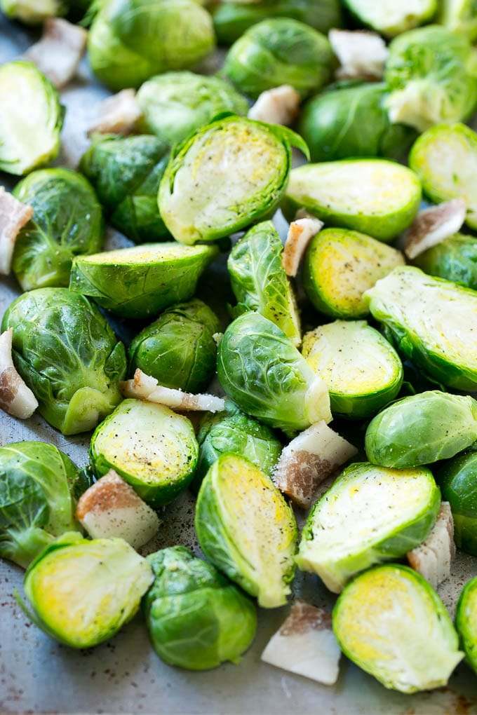 Raw halved brussels sprouts with uncooked bacon on a sheet pan.