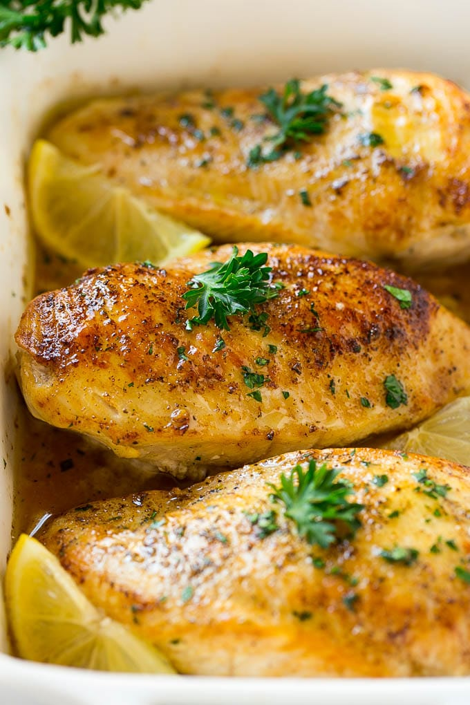 Baked lemon chicken in a white dish topped with herbs.