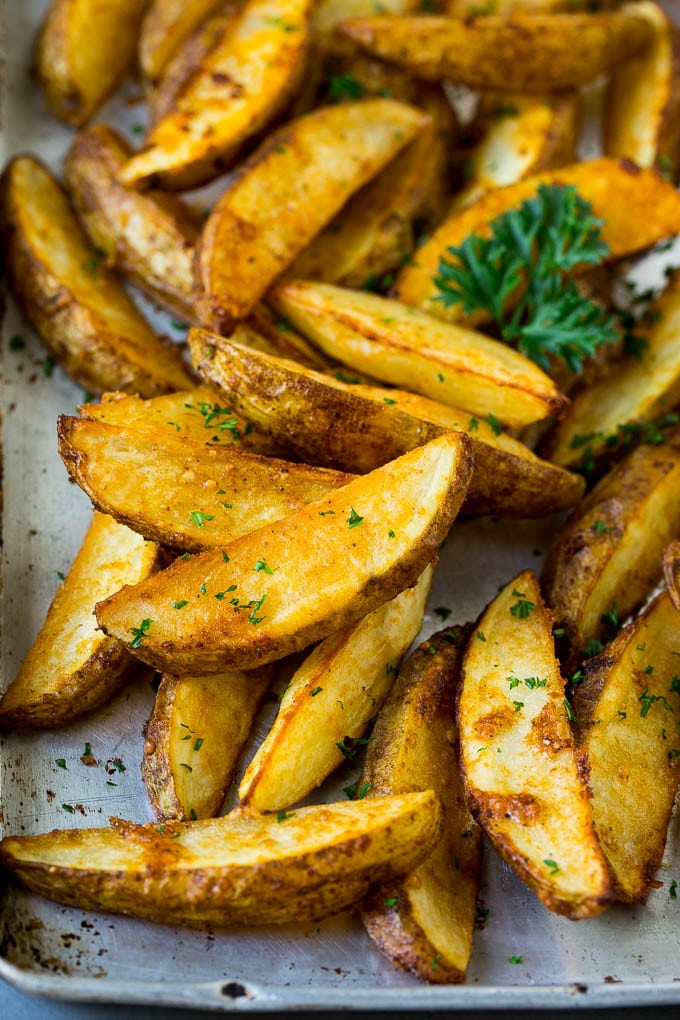 Baked potato wedges on a sheet pan, garnished with fresh parsley.