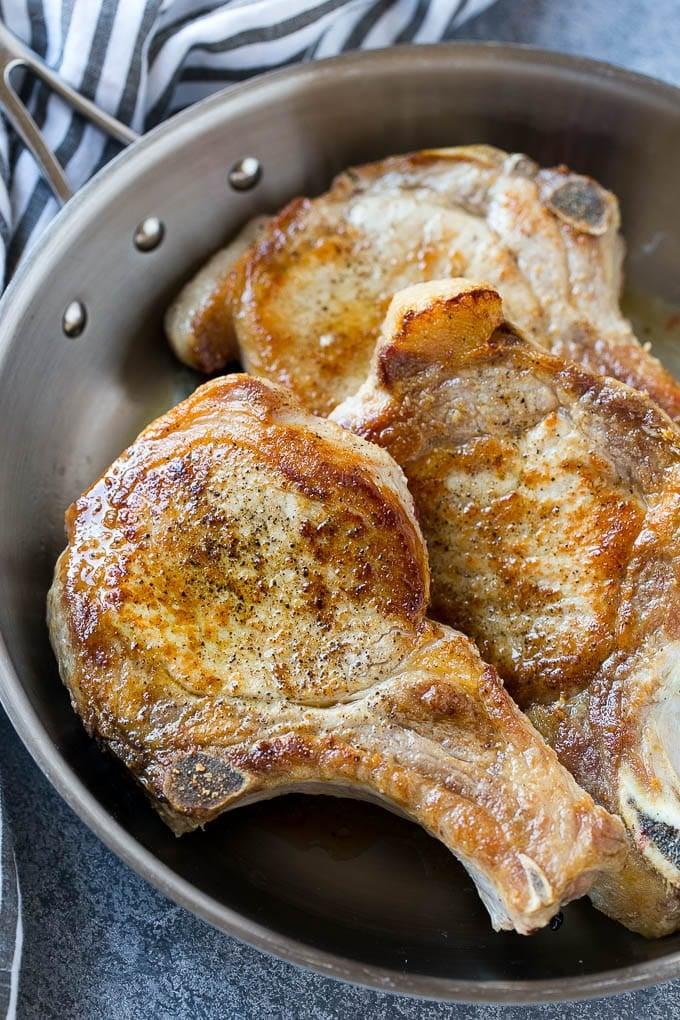 Browned bone in pork chops in a frying pan.