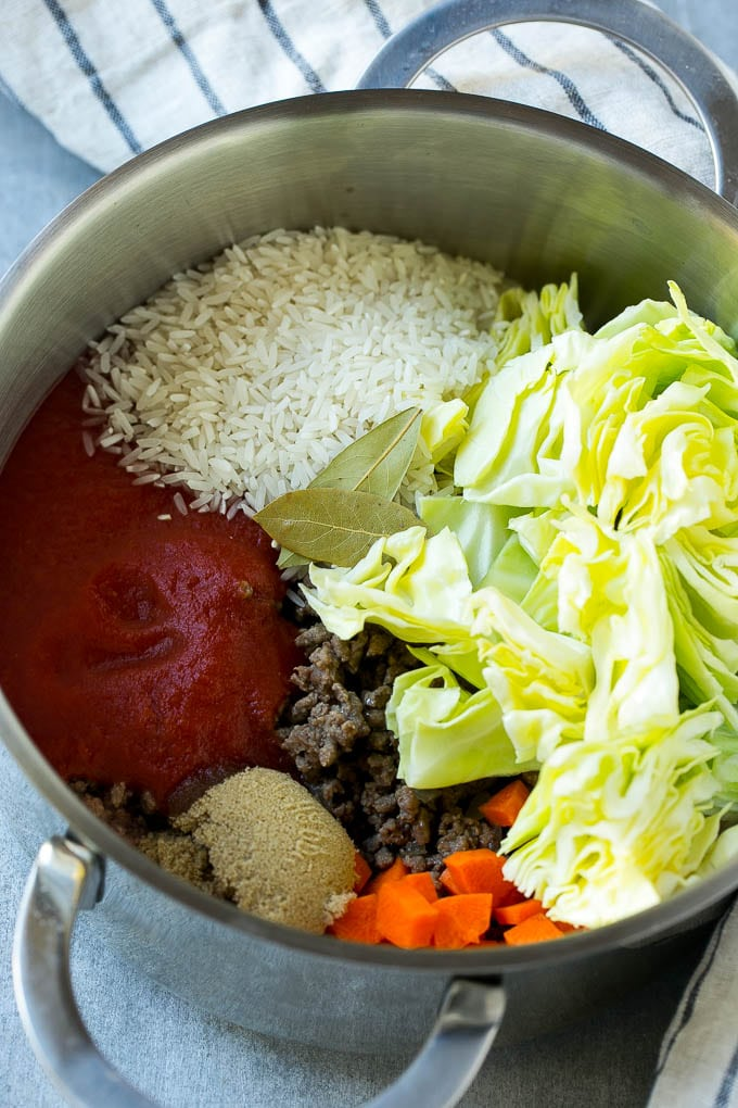 Ingredients for cabbage roll soup including beef, cabbage, vegetables and spices, all in a soup pot.