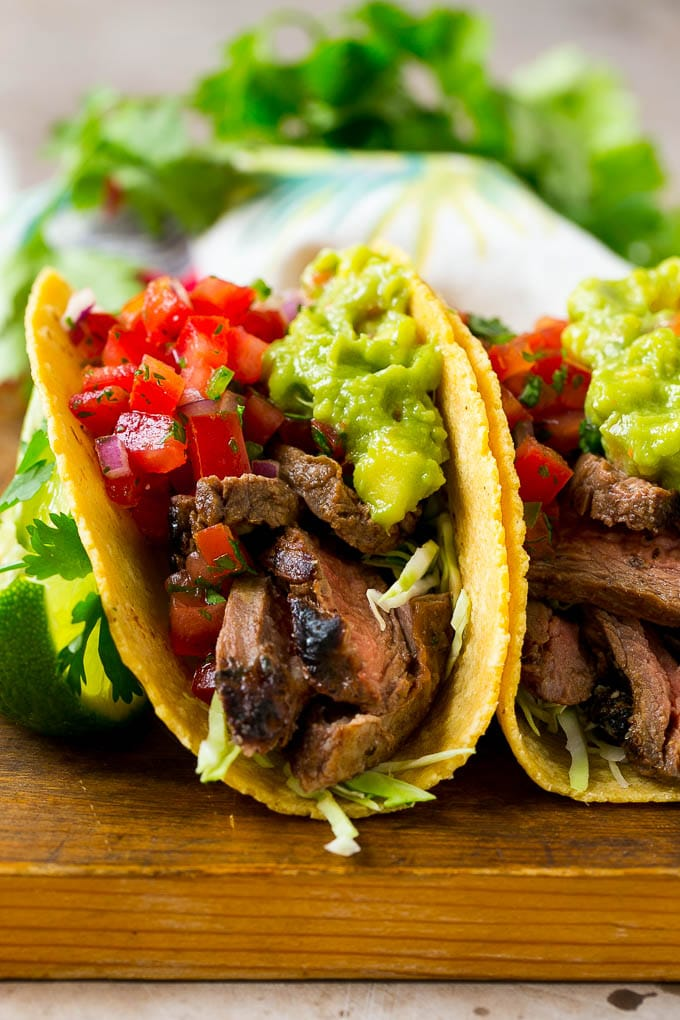 Carne asada tacos in corn tortillas, topped with salsa and guacamole.