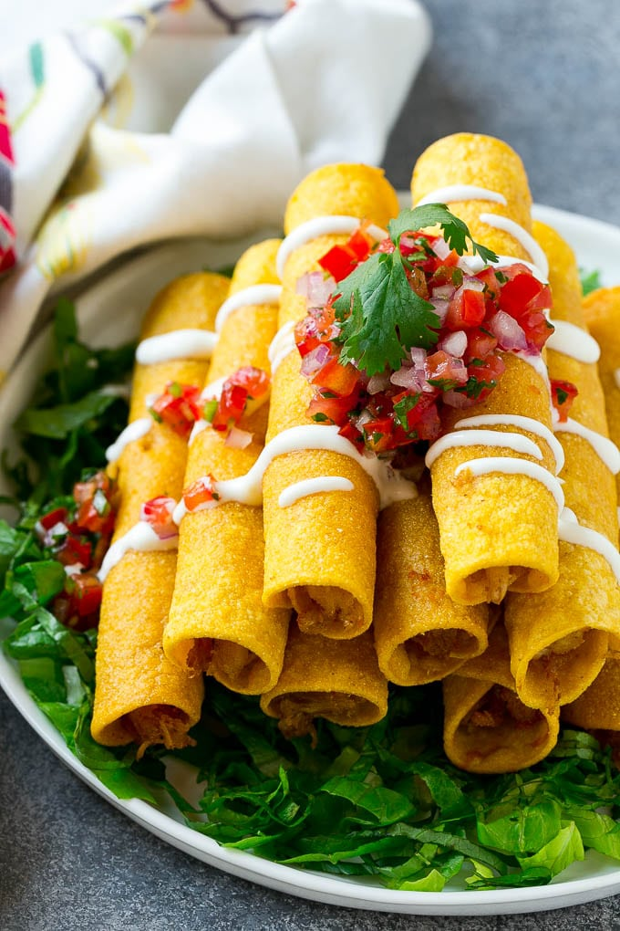 A stack of chicken taquitos with a drizzle of sour cream and pico de gallo topping.