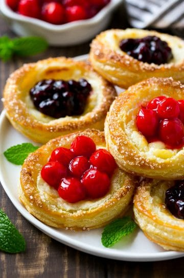 A platter of cream cheese danish topped with fruit.