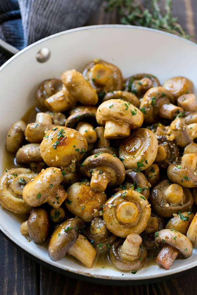 A pan full of cooked mushrooms coated in garlic butter.