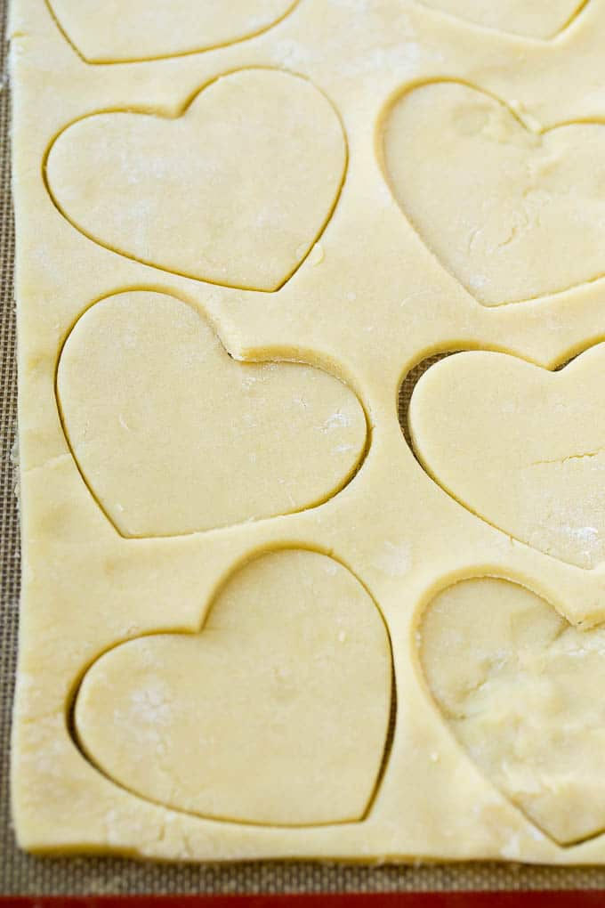 A sheet of sugar cookie dough with heart shaped cut outs.
