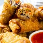 A plate of homemade egg rolls with dipping sauce.
