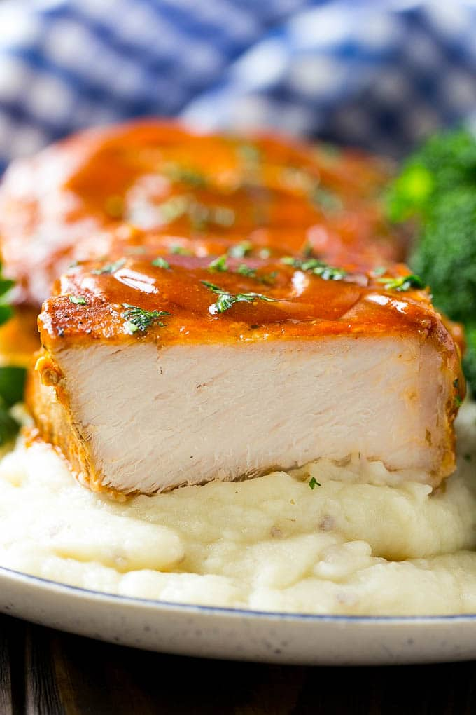 A cross section of a honey garlic pork chop served on mashed potatoes.