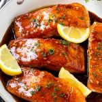 A pan of honey garlic salmon topped with a savory sauce and garnished with parsley and lemon.