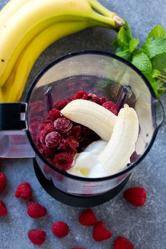 All of the ingredients for raspberry smoothies inside a blender.