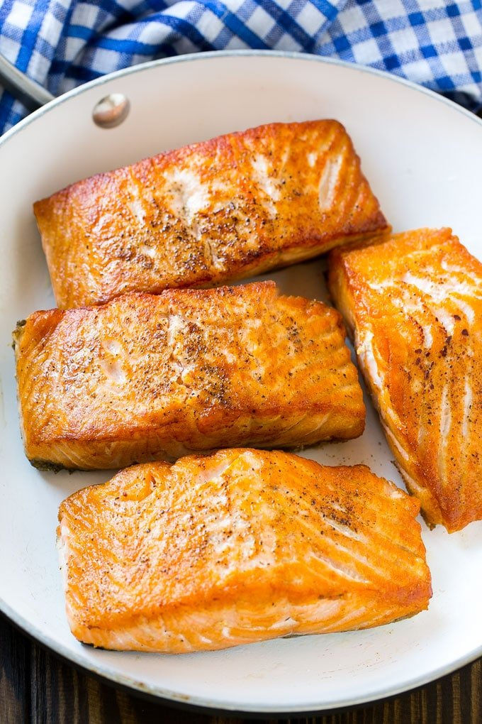 Cooked salmon fillets in a frying pan.