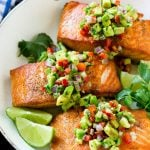 Salmon with avocado salsa in a frying pan.
