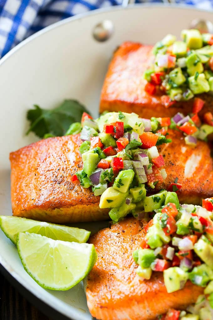 A pan of seared salmon with avocado salsa on top.