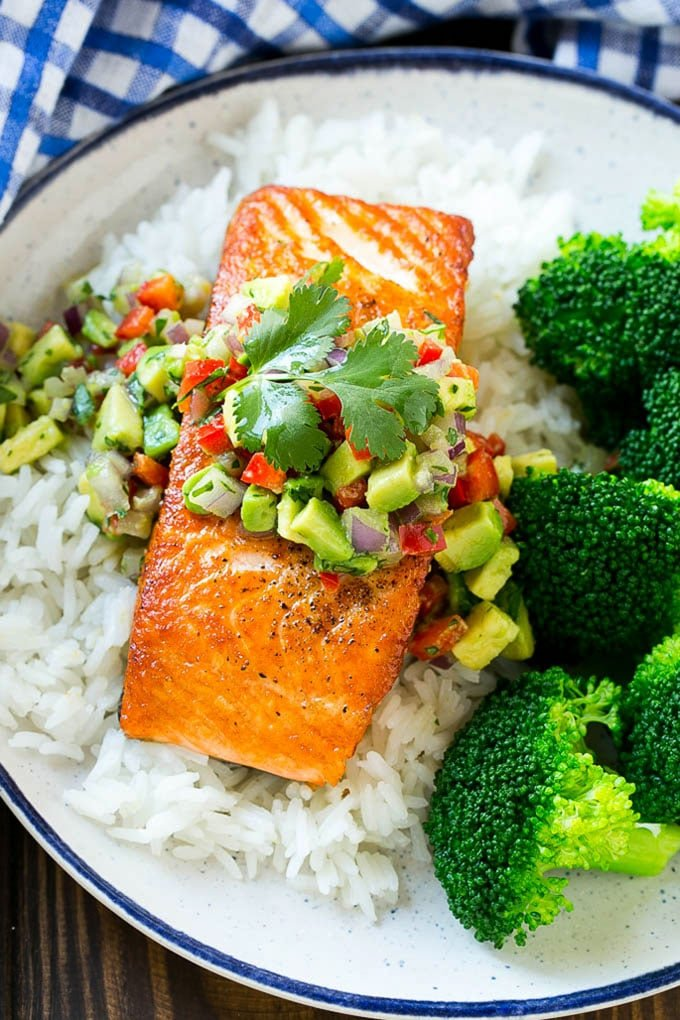 A salmon fillet with avocado salsa served over rice and broccoli.