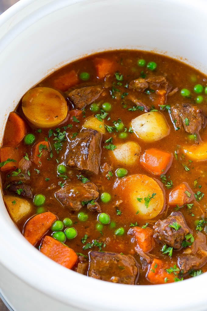 A slow cooker full of beef stew that contains meat, potatoes, carrots and peas, all in a savory broth.