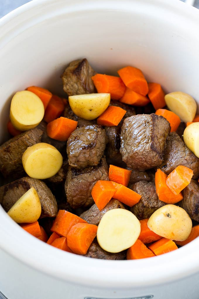 Browned beef, potatoes and carrots in a slow cooker, ready to be turned into beef stew.
