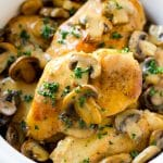 A slow cooker full of cooked chicken breasts topped with marsala wine and mushroom sauce.