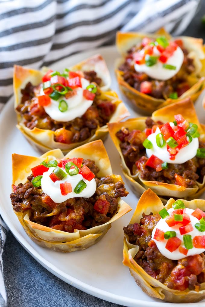 A plate of taco cups made with wontons, seasoned ground beef and cheese, then topped with sour cream, tomatoes and green onions.