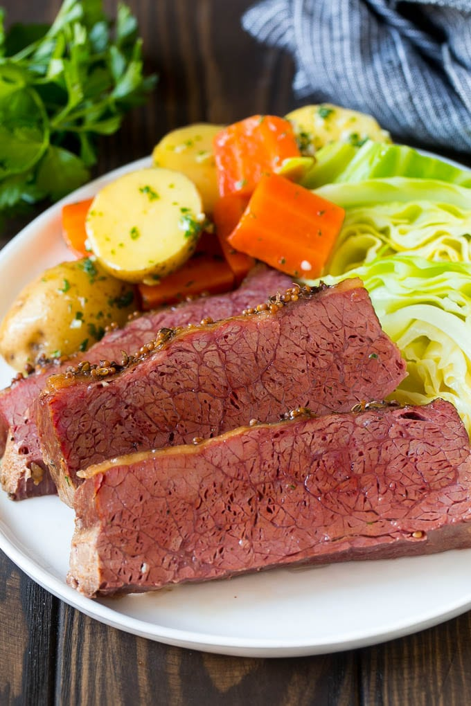 Sliced slow cooker corned beef on a plate with carrots, potatoes and cabbage.