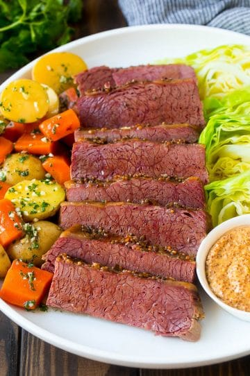 A platter of slow cooker corned beef, cabbage wedges, potatoes and carrots.