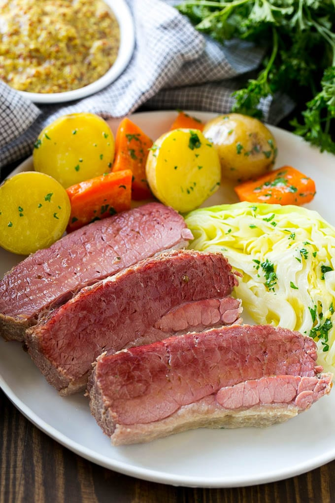 A plate of sliced corned beef with cabbage, carrots and potatoes.