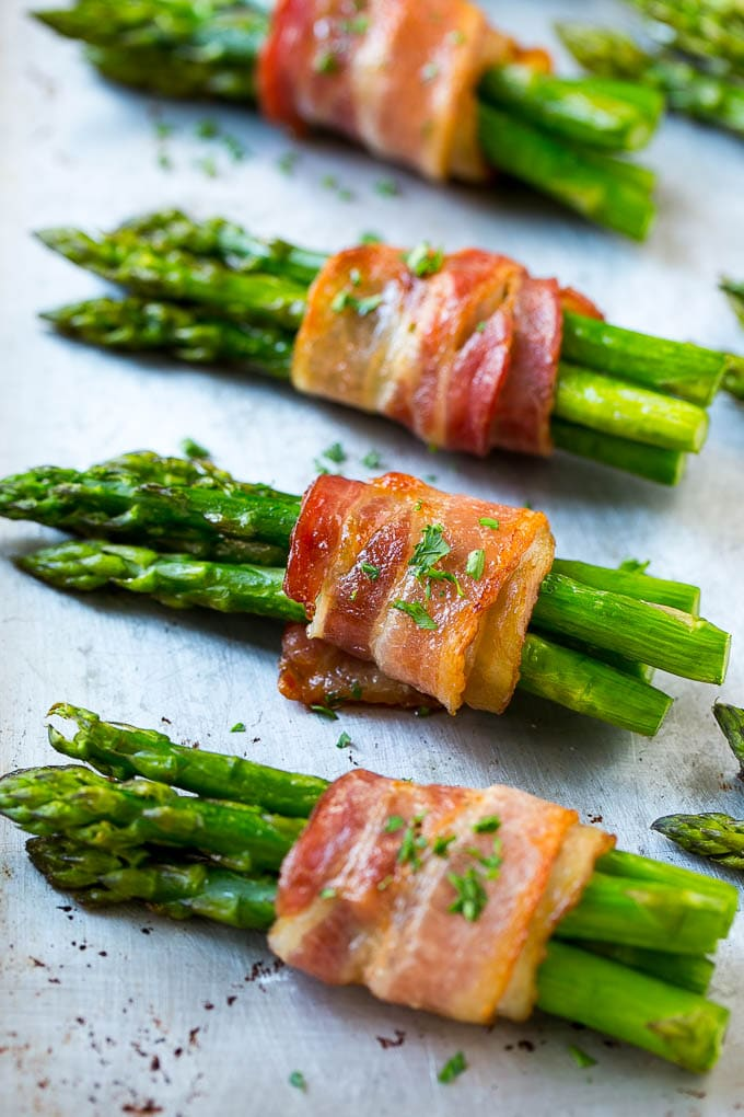 Roasted bacon wrapped asparagus on a sheet pan.