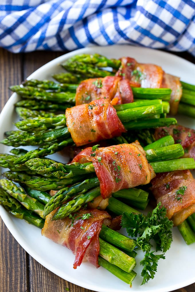 A plate of bacon wrapped asparagus bundles garnished with parsley.