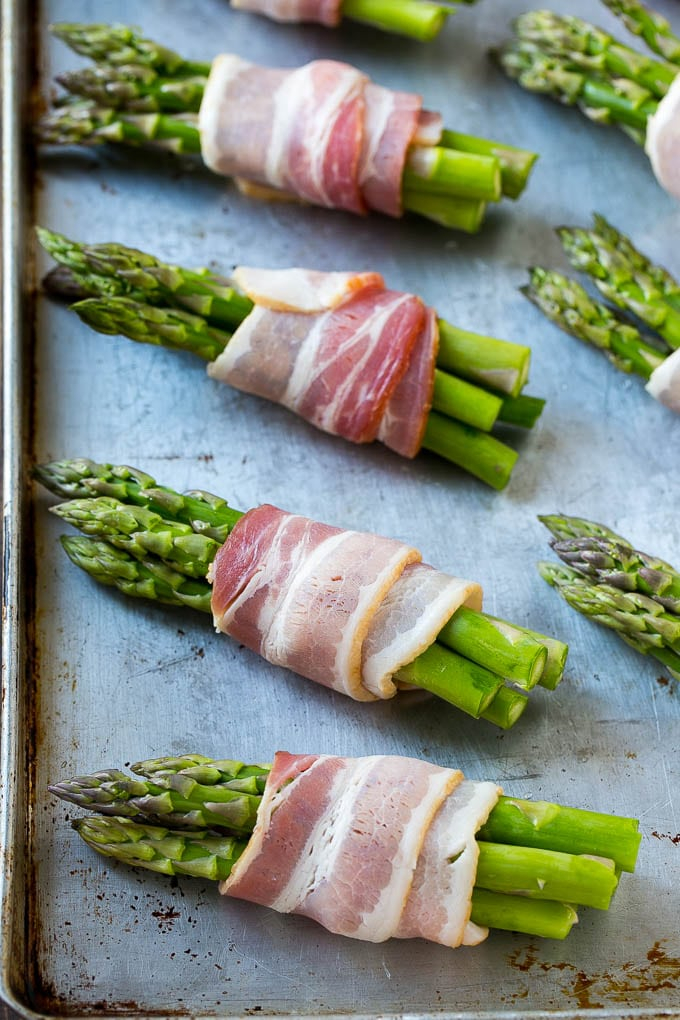 Raw asparagus wrapped in bacon on a sheet pan.