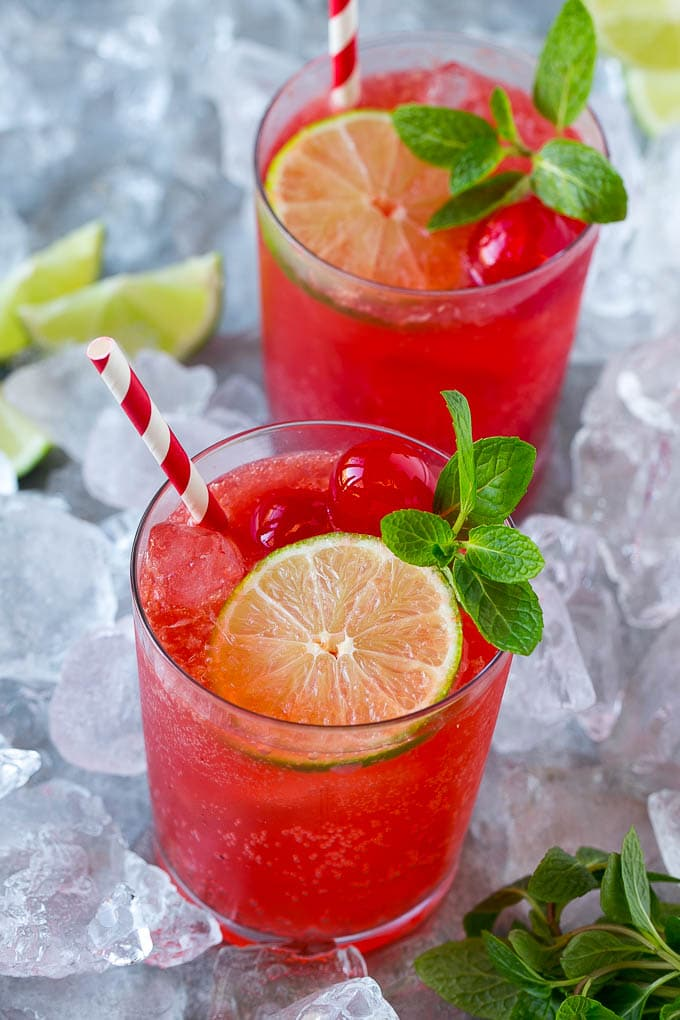 Cups of cherry limeade garnished with mint, lime and cherries.