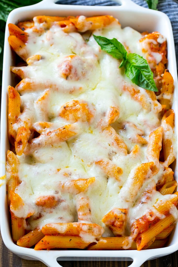 A pan of baked chicken parmesan pasta covered in melted cheese.