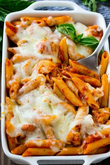 Chicken parmesan pasta in a baking dish topped with melted cheese and garnished with fresh basil.